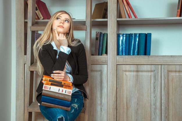 美しい少女は図書館の木製の階段に座って、たくさんの本を持って、目をそらして考えています