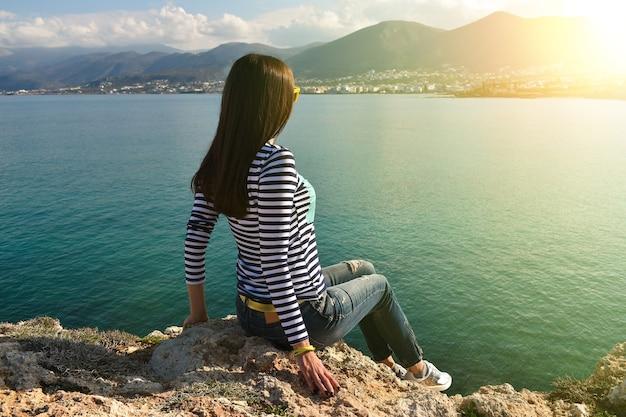 Красивая девушка сидит на скале и смотрит на море