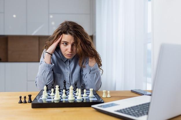家に座って、ラップトップでオンラインでチェスをしている美しい少女