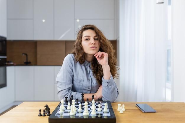 家に座ってチェスをしている美しい少女