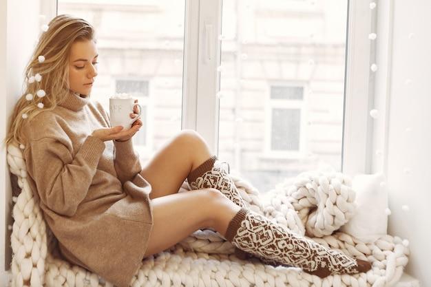 窓の近くで家に座っている美しい少女