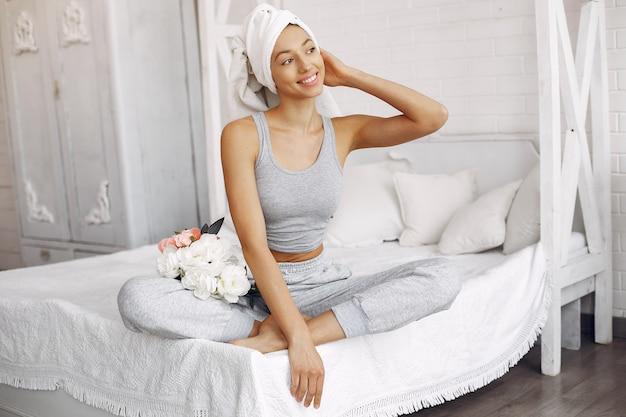自宅のベッドの上に座って美しい少女