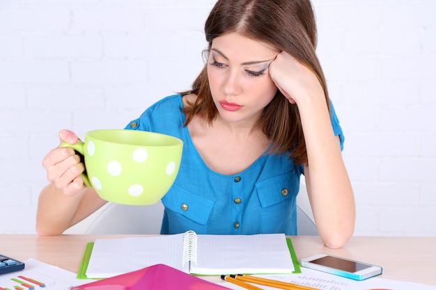 大きなカップでテーブルに座っている美しい少女