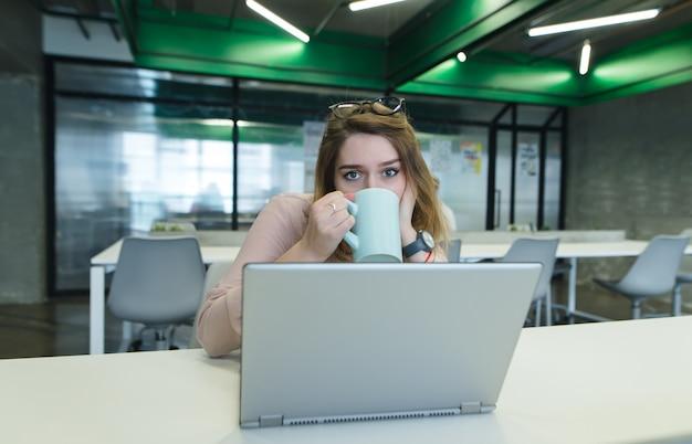 コンピューターの作業中にオフィスの机に座って、カップからコーヒーを飲みながら美しい少女。