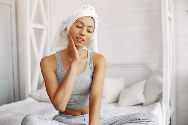 Beautiful girl sitting on a bed using beauty products