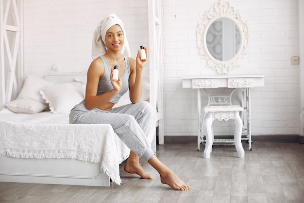 Beautiful girl sitting on a bed with beauty products