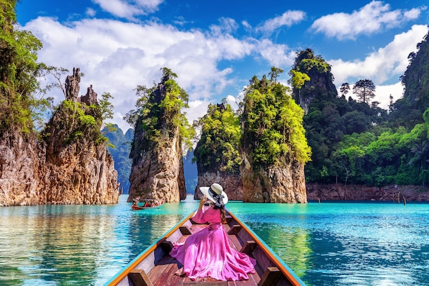 Beautiful girl sitting on the boat and looking to mountains in ratchaprapha dam at khao sok national park, surat thani province, thailand.