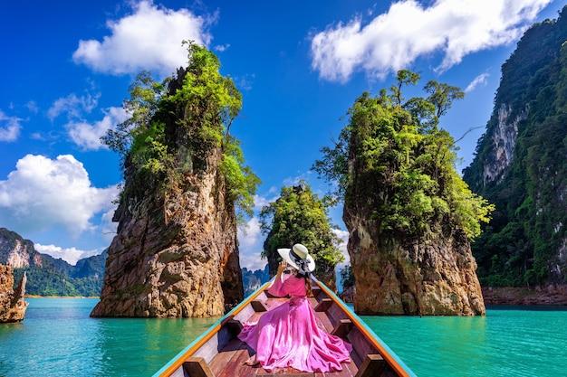 Bella ragazza seduta sulla barca e guardando alle montagne nella diga di ratchaprapha al parco nazionale di khao sok, provincia di surat thani, thailandia.