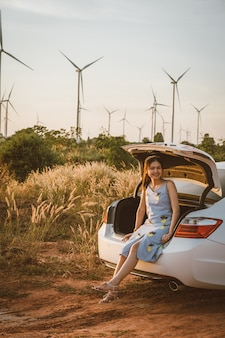 Beautiful girl sitting behind the car and she smiled at twilight background is a wind turbine.