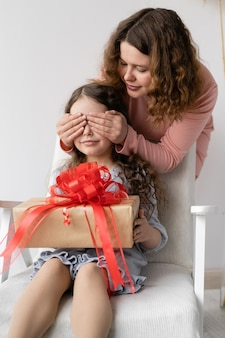 Beautiful girl sitting in a chair. in her hands is a box with a gift and a red bow.