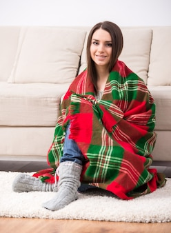 Beautiful girl sitting on floor at home wrapped a blanket.