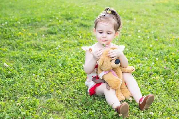 Bella ragazza che si siede nel giardino che tiene orsacchiotto guardando fiore