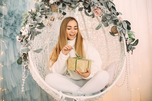 Красивая девушка сидит в студии с подарками