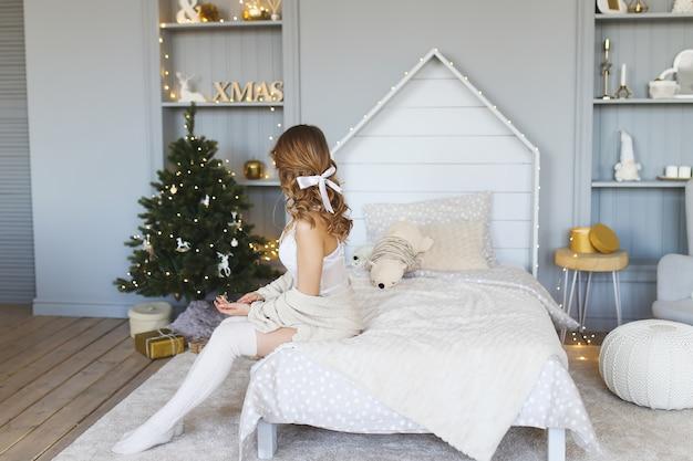 Красивая девушка сидит в постели на фоне елки
