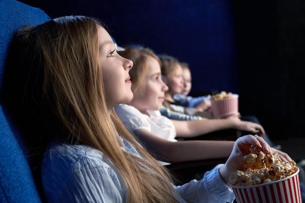 영화관에 앉아서 영화를 보는 아름다운 소녀
