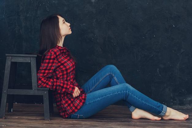 Красивая девушка сидит возле лестницы