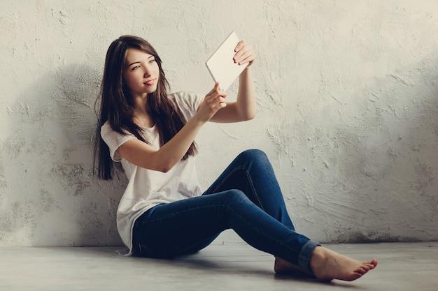 Красивая девушка сидит у стены и смотрит в планшет