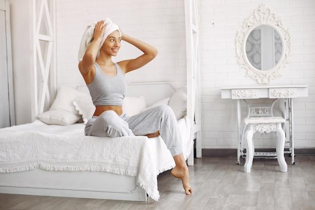 Красивая девушка сидит на кровати с косметикой