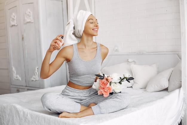 美容製品とベッドの上に座っている美しい少女