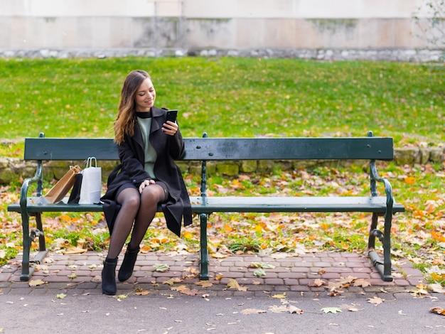 ベンチに座っている美しい少女、携帯電話を持った女性がソーシャルネットワークにメッセージを書き、公園で晴れた秋の日、買い物の後にリラックスした女性。