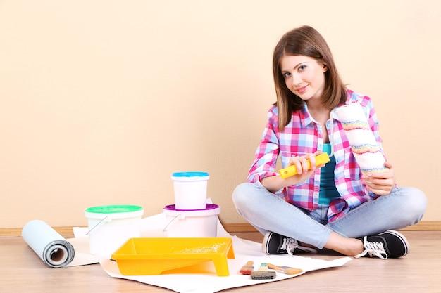 壁を塗るための機器が付いている床に座っている美しい少女