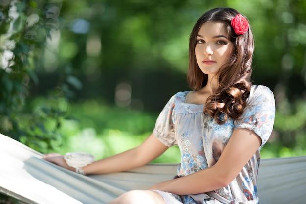 ハンモックをぶら下げに座っている美しい女の子