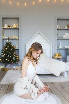Красивая девушка сидит на полу на фоне елки