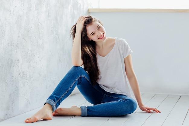 Красивая девушка сидит на полу