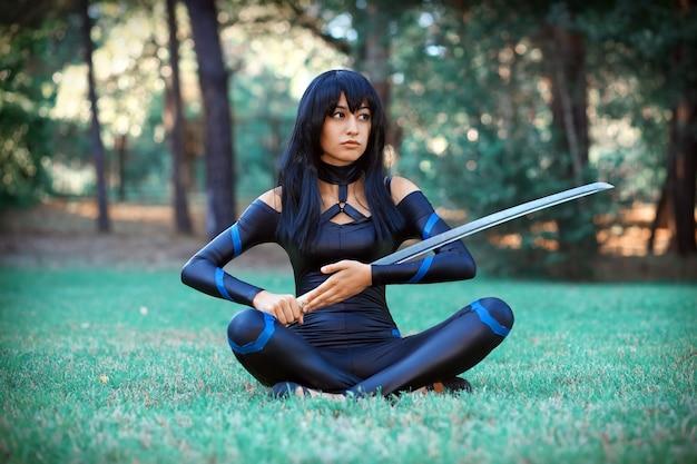 Красивая девушка сидит на траве и держит самурайский меч. оригинальный косплей персонажа