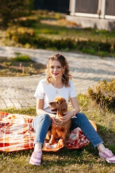 Красивая девушка сидит на улице и играет со своей собакой