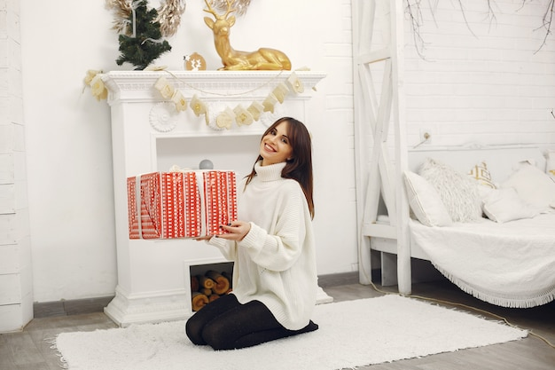Beautiful girl sitting in a room with christmas gifts