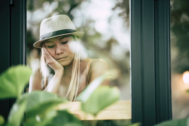 Beautiful girl sitting sad at the window in cafe
