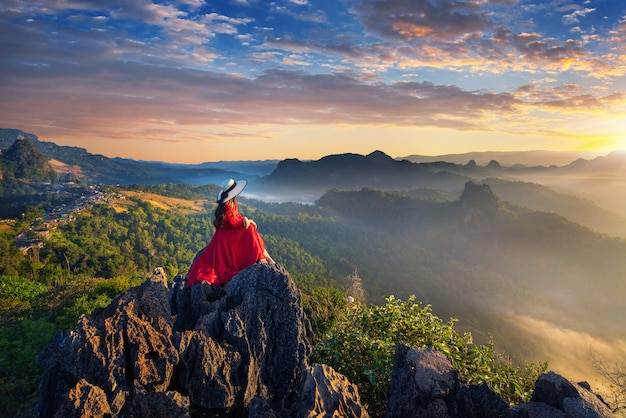 Beautiful girl sitting on sunrise viewpoint at ja bo village, mae hong son province, thailand