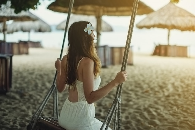 Beautiful girl sitting on a swing and watching the sunrise