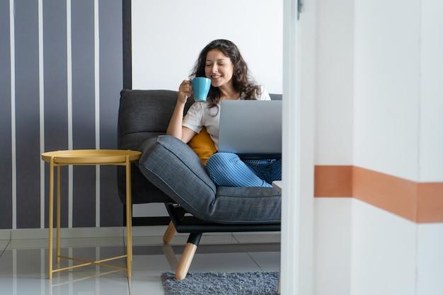 Красивая девушка сидит с ноутбуком на диване в стильной комнате. работа из дома. рабочая атмосфера в хорошем настроении.