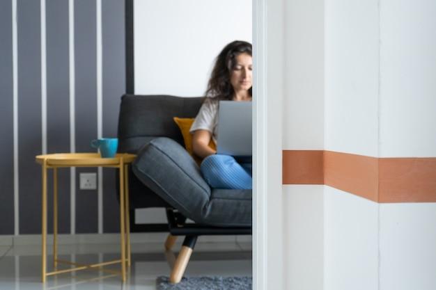 세련 된 방에 소파에 노트북과 함께 앉아 아름 다운 소녀. 집에서 일하십시오. 기분이 좋은 직장 분위기