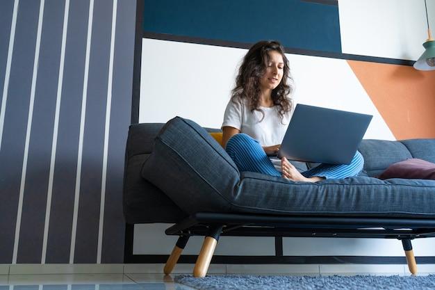 세련 된 방에 소파에 노트북과 함께 앉아 아름 다운 소녀.