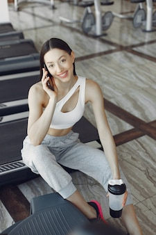 A beautiful girl sitting with phone in a gym