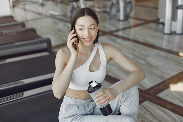 Una bella ragazza seduta con il telefono in una palestra