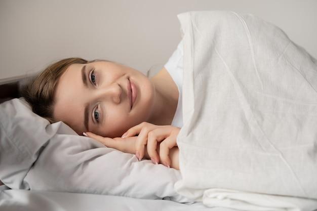 Красивая девушка спит в спальне, крепко спит, отличное здоровье. открытые глаза улыбка на лице