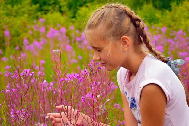 Beautiful girl smells pink flowers in garden