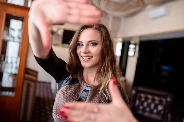 Красивая девушка улыбается и тянет руки к камере.