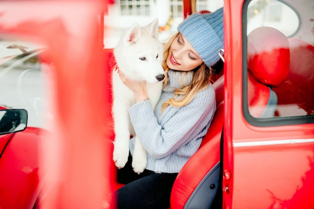 A beautiful girl smiles, caresses her beloved white fluffy dog in winter in a red car.
