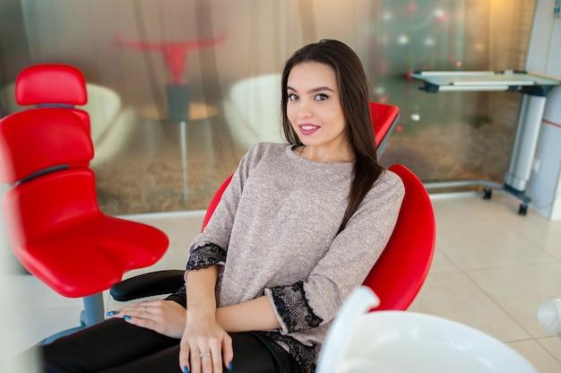美しい少女は歯科用椅子で微笑む。