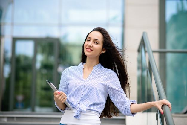 Красивая девушка улыбается и работает на планшете.