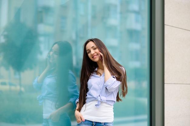 笑顔で電話で話している美しい女の子。
