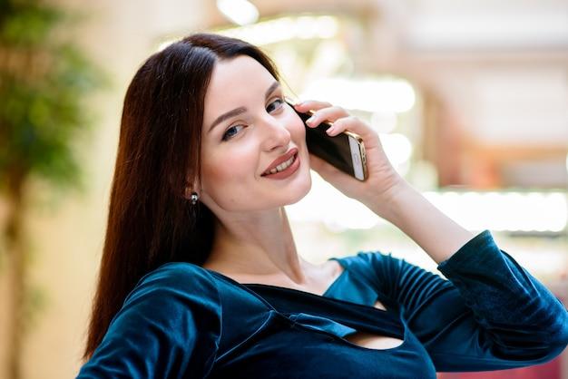 Красивая девушка улыбается и разговаривает по телефону.