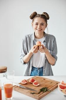 白い壁にグレープフルーツの部分を保持笑みを浮かべて美しい少女。健康的なフィットネス栄養。