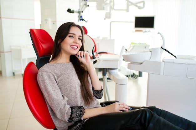 Красивая девушка улыбается в стоматологии.