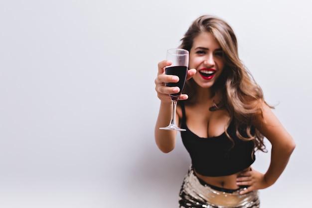 Bella ragazza sorridente e alzando il bicchiere di vino in pane tostato. indossa gonna con paillettes, top nero. look sexy ed elegante con pancia nuda e scollatura profonda. concentrarsi sul bicchiere di vino rosso. isolato.